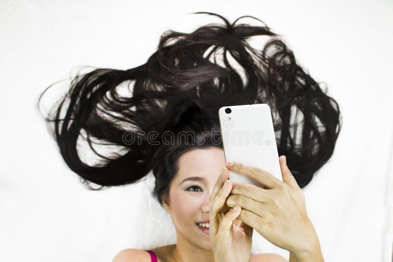 Zbliżenie portret szczęśliwe azjatykcie kobiety kłama na ziemi z czarny długie włosy działający uśmiech i kursowanie tel obrazy stock