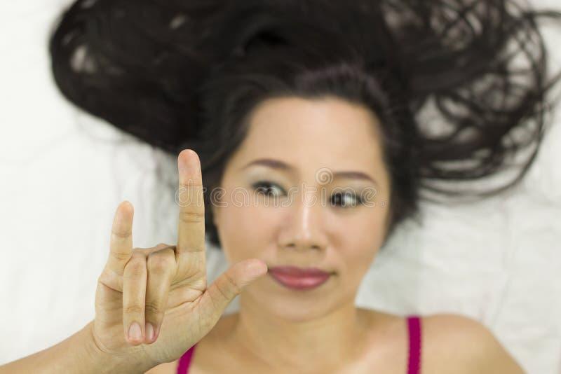Zbliżenie portret szczęśliwe azjatykcie kobiety kłama na ziemi z czarny długie włosy działający uśmiech, zabawa obrazy stock