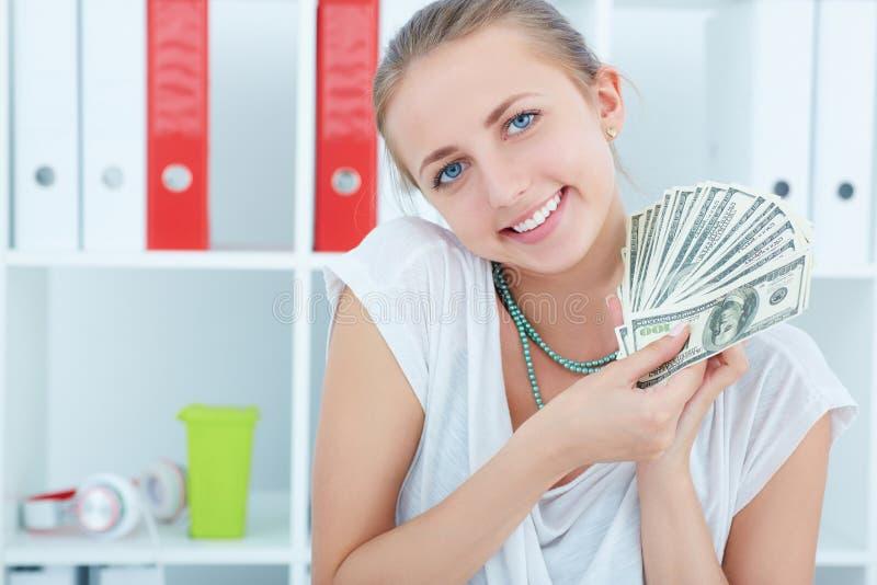 Zbliżenie portret szczęśliwego z podnieceniem pomyślnego młodego biznesowej kobiety mienia pieniądze dolarowi rachunki w ręce obraz stock
