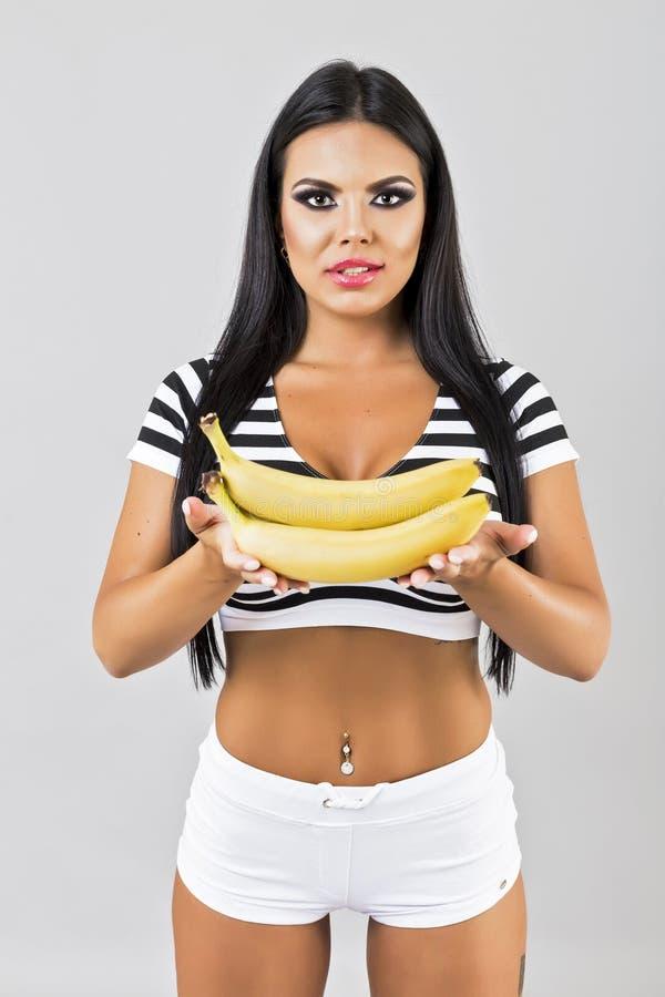 Zbliżenie portret szczęśliwi młodej kobiety mienia banany zdjęcia stock