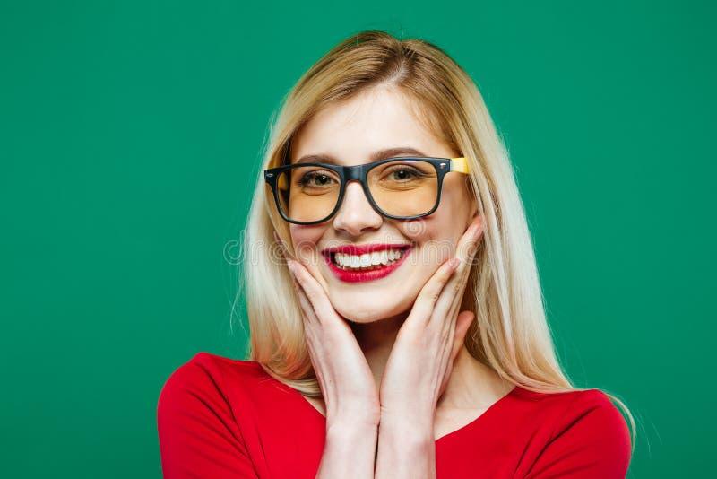 Zbliżenie portret Uśmiechnięta dziewczyna w Eyeglasses i Czerwonym wierzchołku na Zielonym tle Młoda blondynka z Długie Włosy i P fotografia stock