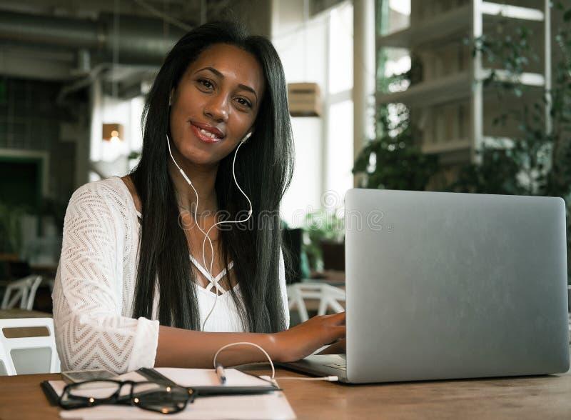 Zbliżenie portret uśmiechnięty młody afrykański kobiety obsiadanie w kawiarni z laptopem zdjęcie stock