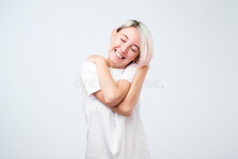 Zbliżenie portret, ufna kobieta herself w białym koszulki mienia przytuleniu, odosobniony biały tło zdjęcia stock
