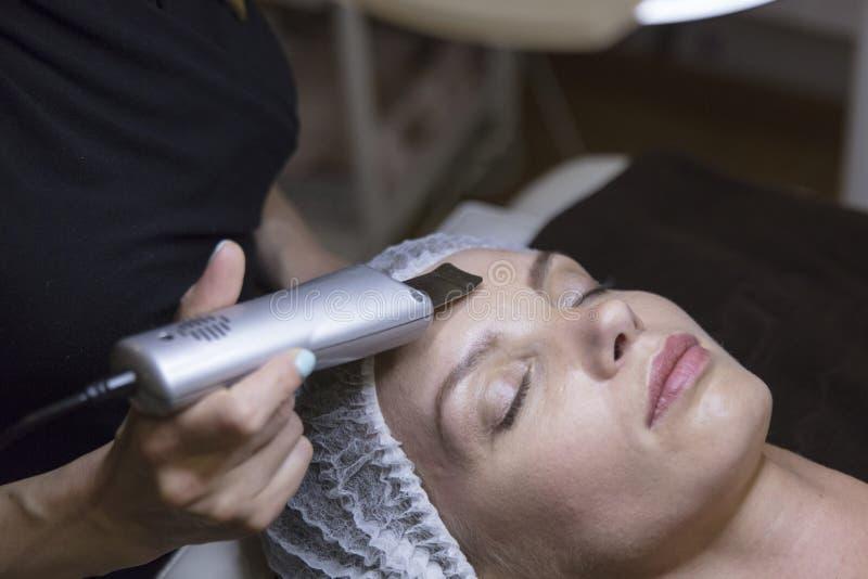 Zbliżenie portret urocza kobieta i ręka z kosmetyczną podnośnego przyrządu procedurą dotyka jej twarz obrazy stock