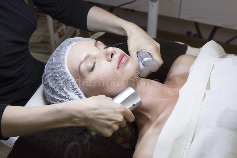 Zbliżenie portret urocza kobieta i ręka z kosmetycznym radiowym podnośnym przyrządem dotyka jej twarz fotografia stock