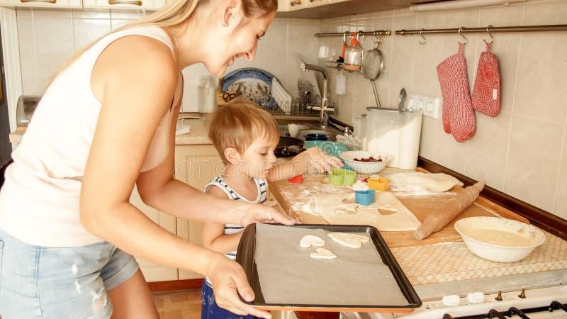 Zbli?enie portret urocza 3 lat berbecia ch?opiec robi ciastkom z matk? dziecko trzyma wypiekow? nieck? i k?adzenie zdjęcia stock