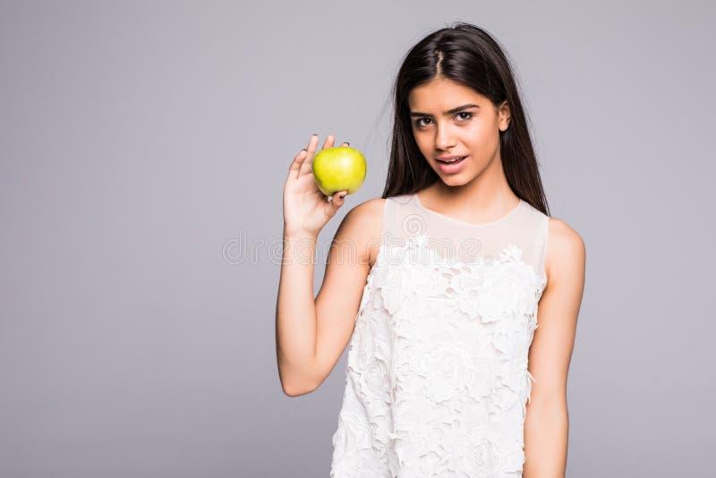 Zbliżenie portret urocza młoda brunetki kobieta gryźć soczystego świeżego wyśmienicie jabłka przeciw szaremu tłu fotografia stock