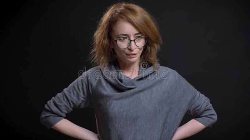 Zbliżenie portret w średnim wieku ekstrawagancka rudzielec kobieta w szkłach udaremnia wewnątrz i mieć ręki na biodrach zdjęcie stock