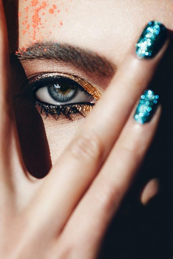 Zbliżenie portret z głębokim niebieskim okiem, kreatywnie makeup i ręką, fotografia stock