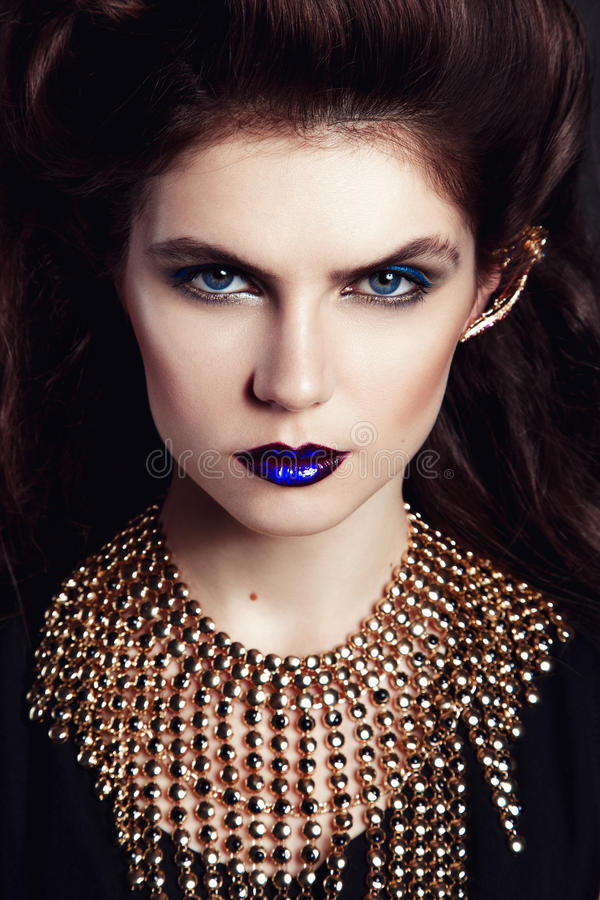 Zbliżenie portret z głębokim niebieskim okiem, kreatywnie makeup i złotymi akcesoriami, zdjęcia stock
