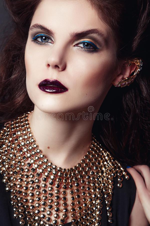 Zbliżenie portret z głębokim niebieskim okiem, kreatywnie makeup i złotymi akcesoriami, obrazy stock