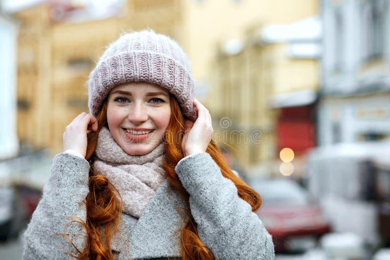 Zbliżenie portret zadowolona czerwona z włosami dziewczyna jest ubranym dziający ciepłego obrazy stock