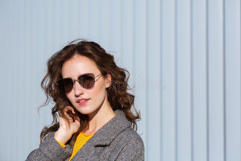 Zbliżenie portret zadowolonego modnisia wzorcowi jest ubranym okulary przeciwsłoneczni i żakiet, pozuje blisko żaluzji Przestrzeń obraz royalty free
