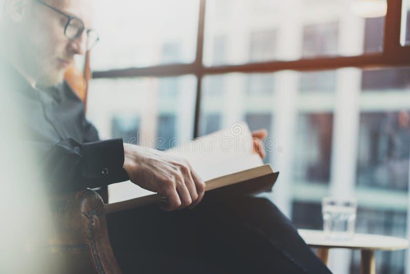 Zbliżenie portret zadumanego brodatego biznesmena czytelnicza książka podczas gdy siedzący w rocznika krześle stary złagodzone po obrazy royalty free
