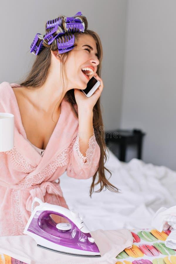 Zbliżenie portreta ładna dziewczyna z długie włosy w różowym bathrobe i curler na głowie przy prasowaniem odziewa w domu Ona mówi obrazy stock