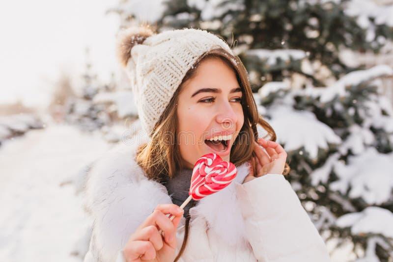 Zbliżenie portreta śliczna śmieszna dziewczyna w białym woolen kapeluszu ma zabawę z różowym kierowym lollypop na ulicie pi?kne k zdjęcie stock