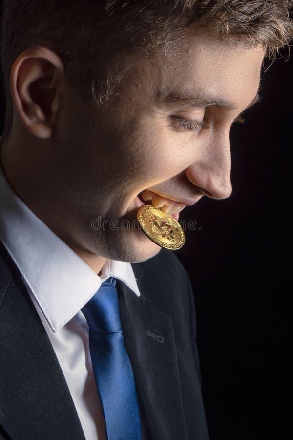 Zbliżenie portreta biznesmena handlowa mienia bitcoin szczęśliwy młody atrakcyjny cryptocurrency, odizolowywający na czerni fotografia royalty free