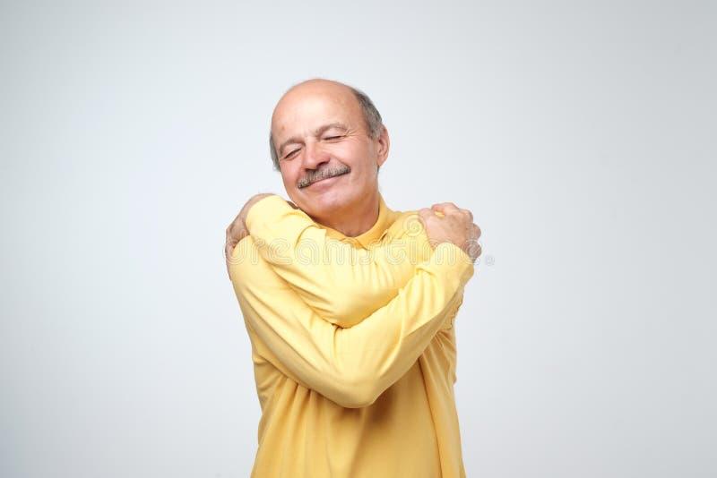 Zbliżenie portreta mężczyzna ufny uśmiechnięty przytulenie himself Jestem najlepszy pojęciem fotografia stock