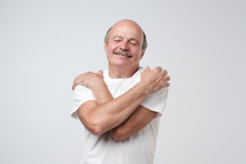 Zbliżenie portreta mężczyzna ufny uśmiechnięty przytulenie himself Jestem najlepszy pojęciem obraz stock