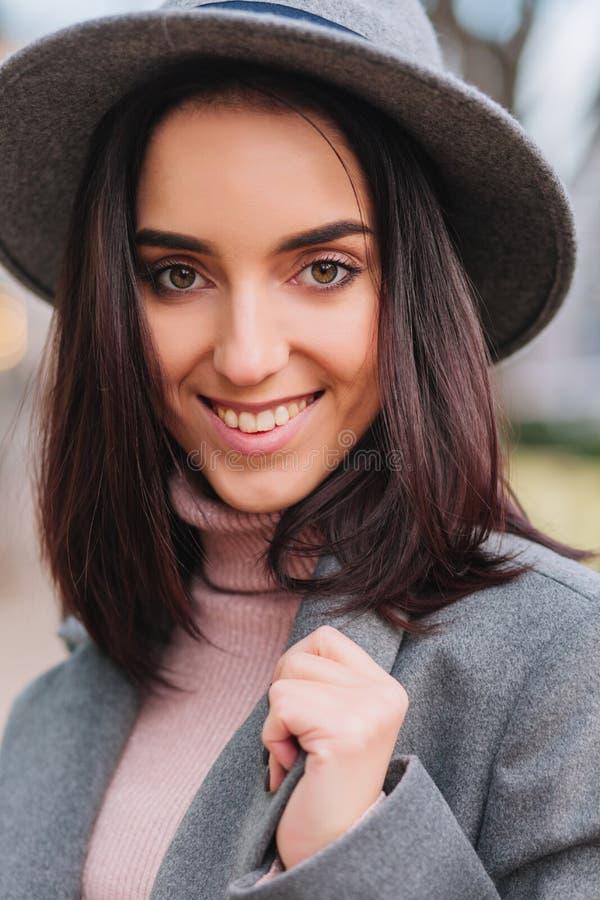 Zbliżenie portreta modna powabna młoda kobieta z brunetka włosy w popielaty kapeluszowy ono uśmiecha się kamera na ulicie w mieśc zdjęcie stock