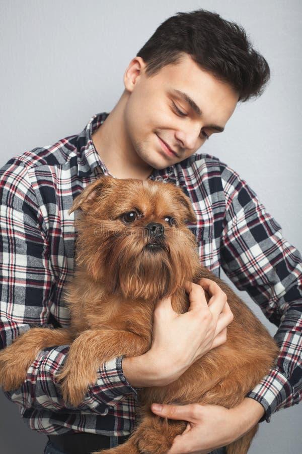 Zbliżenie portreta modnisia przystojny młody mężczyzna, całuje jego dobrego przyjaciel czerwieni psa odizolowywał lekkiego tło Po zdjęcie royalty free