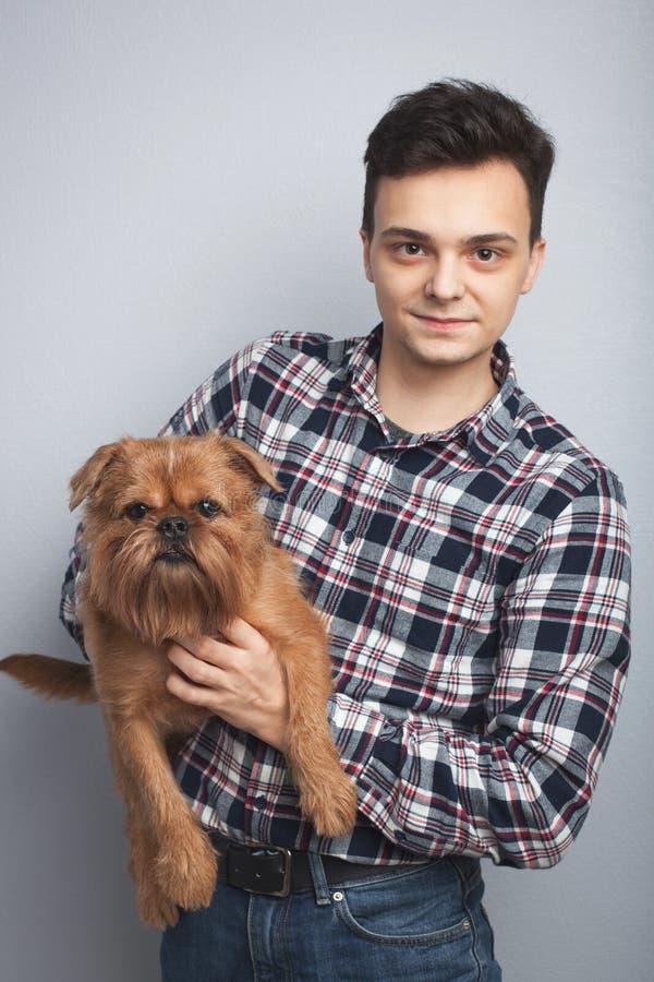 Zbliżenie portreta modnisia przystojny młody mężczyzna, całuje jego dobrego przyjaciel czerwieni psa odizolowywał lekkiego tło Po zdjęcia royalty free