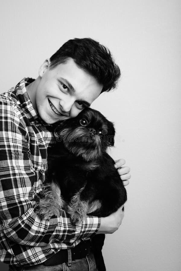 Zbliżenie portreta modnisia przystojny młody mężczyzna, całuje jego dobrego przyjaciela czarnego psa odizolowywał lekkiego tło Po zdjęcia stock