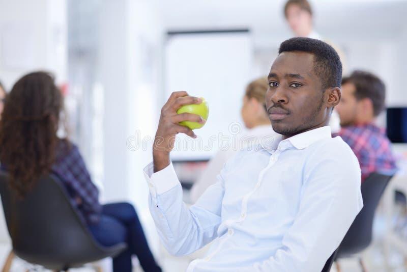 Zbliżenie portreta poważny biznesowy mężczyzna, dylowy producenta łasowania zieleni jabłko zdjęcie stock