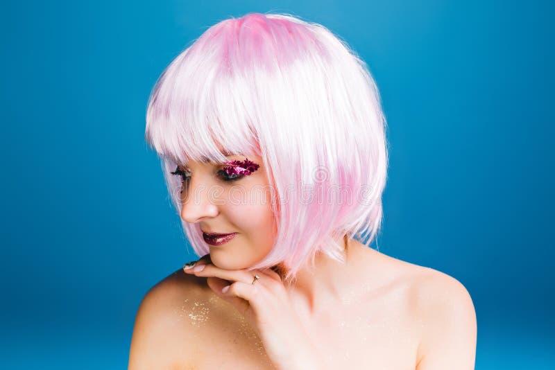 Zbliżenie portreta radosna młoda kobieta z nagimi ramionami, różowy ostrzyżenie ono uśmiecha się popierać kogoś na błękitnym tle  obraz stock