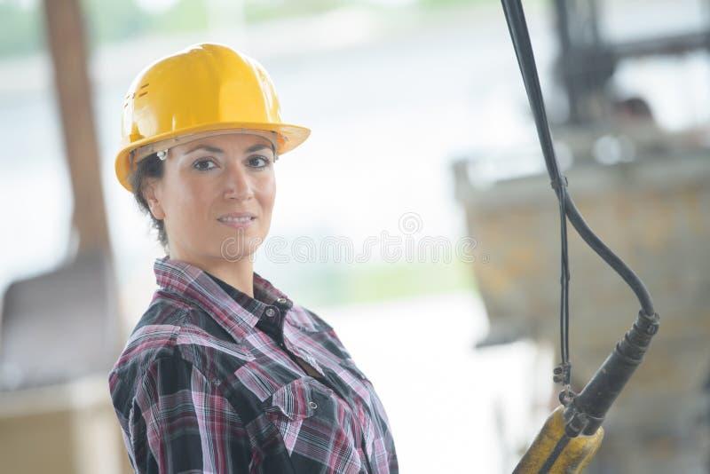 Zbliżenie portreta szczęśliwy żeński pracownik budowlany przy miejscem obraz royalty free