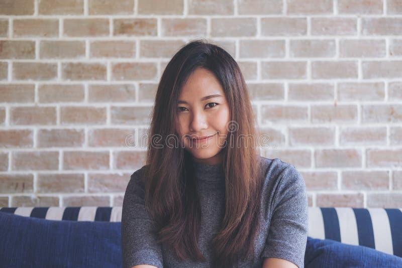 Zbliżenie portreta wizerunek piękna Azjatycka kobieta z smiley twarzy obsiadaniem na kanapie z czuć dobry i relaksuje z cegły ści fotografia stock