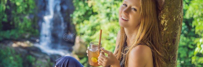 Zbliżenie portreta wizerunek piękna kobieta pije lodowej herbaty z czuć szczęśliwy w zielonym natury i siklawy ogródzie obraz royalty free