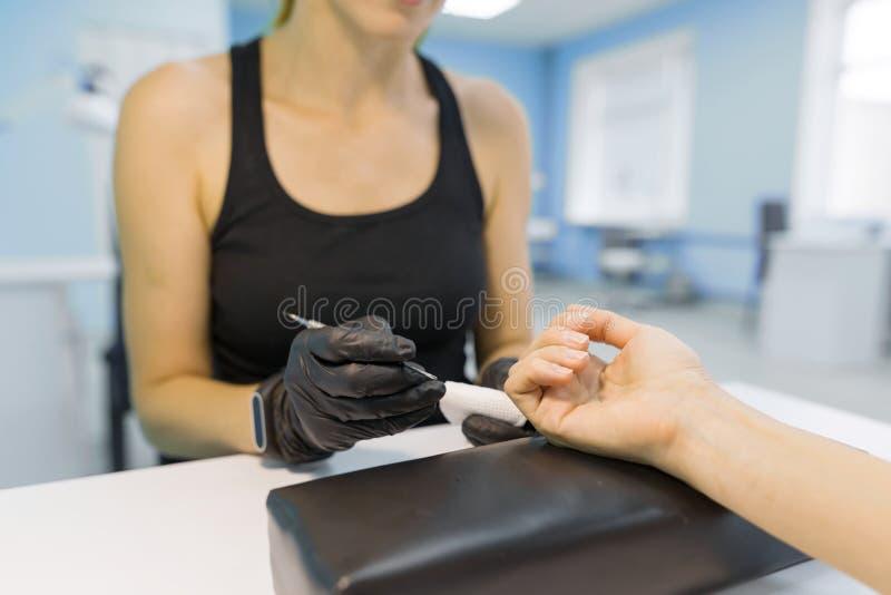 Zbliżenie proces fachowy manicure Manicurzysta kobiety ręki w czarnych rękawiczkach robi manicure'owi używać profesjonalistów nar fotografia royalty free