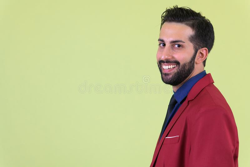 Zbliżenie profilowy widok młody szczęśliwy brodaty Perski biznesmen patrzeje kamerę w kostiumu zdjęcie royalty free