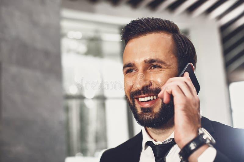 Zbliżenie przystojnego młodego mężczyzny rozmawiającego przez telefon i uśmiechającego się obraz stock