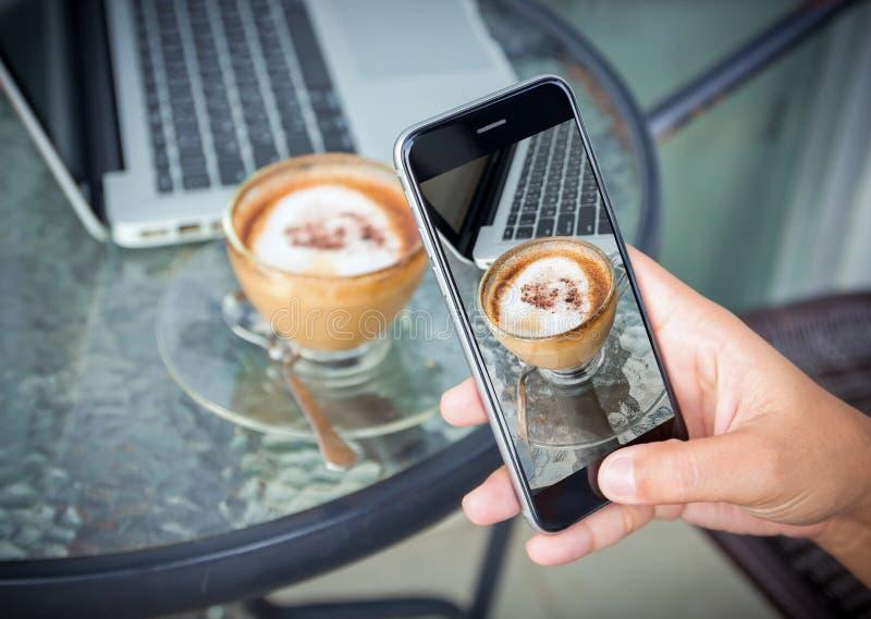 Zbliżenie ręka bierze fotografii kawę na praca stole obrazy stock