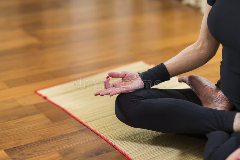 Zbliżenie ręka Kaukaskiej brunetki kobiety Ćwiczy joga Indoors Robić Sukhasana Ćwiczy W Lotosowej terapii pozie Przed zdjęcia royalty free