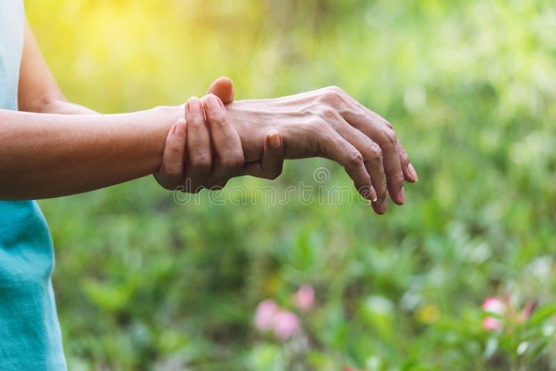 Zbliżenie ręka osoby mienia ręka jego pełnia ból dalej dla zdrowego pojęcia na natury tle obraz stock