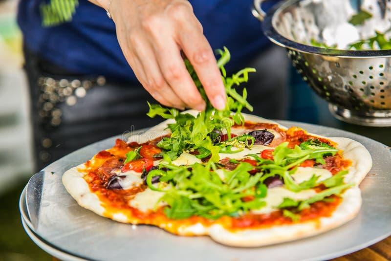 Zbliżenie ręka szef kuchni piekarniana robi pizza przy kuchnią zdjęcie royalty free