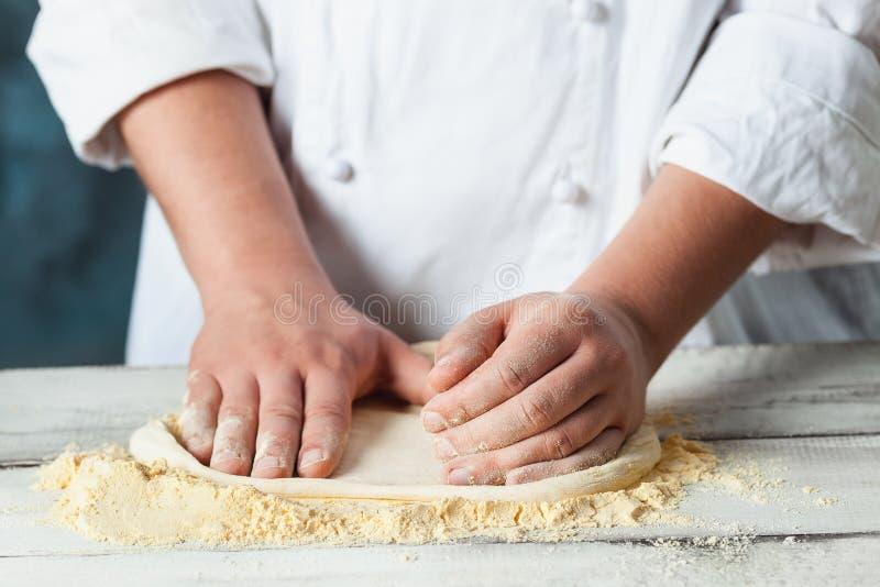 Zbliżenie ręka szefa kuchni piekarz w biel jednolitej robi pizzy przy kuchnią obraz royalty free