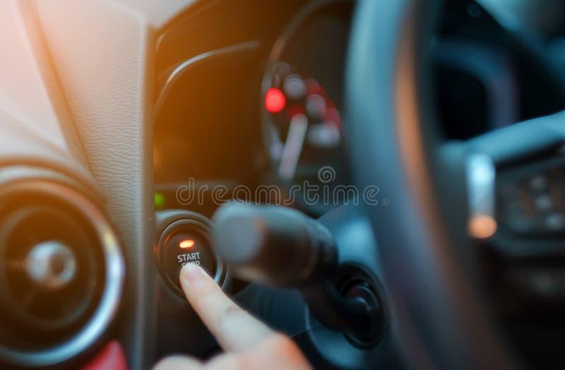 Zbliżenie ręki dosunięcie na samochodowym początku silniku, kobieta kierowca pcha początku guzika zapłonową zmianę w nowożytnym l obrazy royalty free