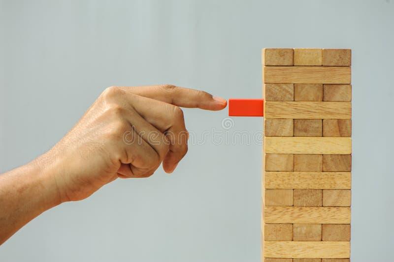 Zbliżenie ręki mężczyzna bierze jeden blok na wierza od drewnianych bloków, fotografia royalty free
