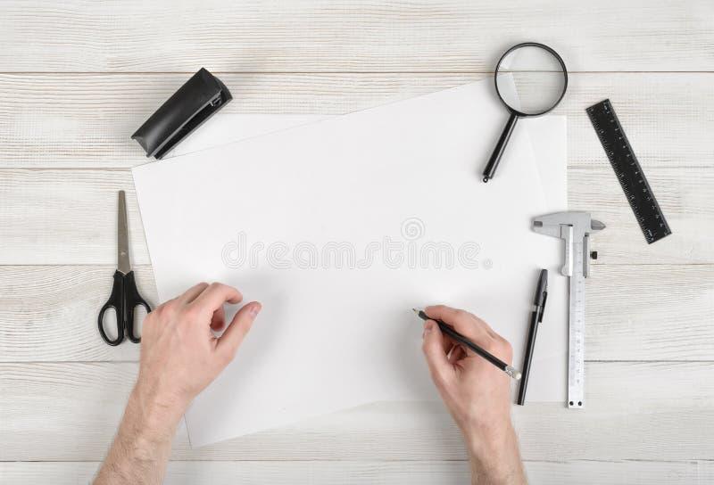 Zbliżenie ręki mężczyzna mienia rysunek na białym papierze w odgórnym widoku i ołówek Draftsman miejsce pracy wyposażający z wład zdjęcia stock
