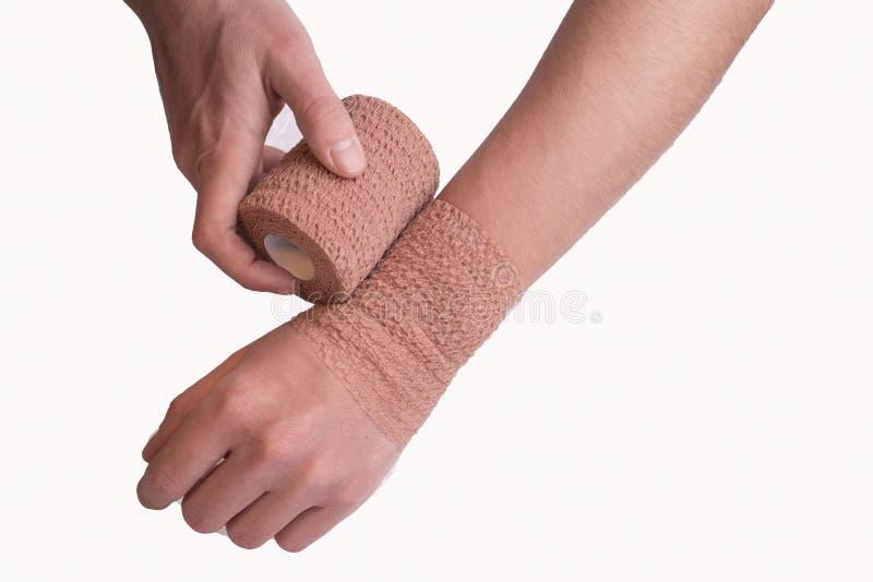 Zbliżenie ręki mężczyzny samozamykający się staw nadgarstkowy na wypadek urazu, z pomocą elastycznego, amerykańskiego bandażu kob obrazy stock