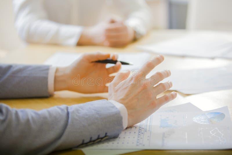 Zbliżenie ręki z pieniężnymi mapami przy biznesowym spotkaniem w biurze zdjęcie stock