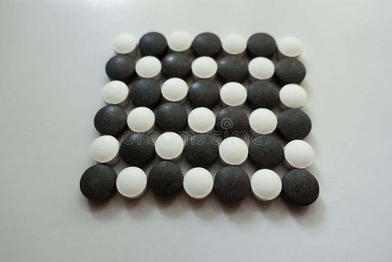Zbliżenie robić czarny i biały pigułki czeka wzór fotografia royalty free