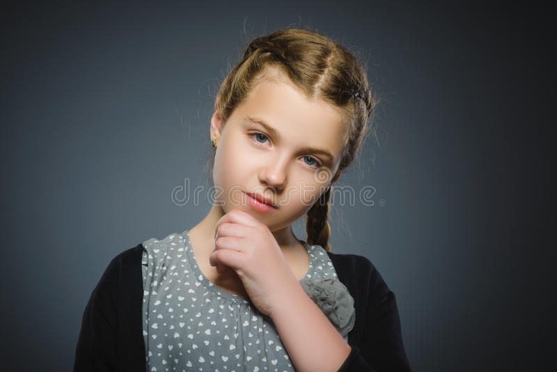 Zbliżenie Rozważna dziewczyna z ręką przy głową odizolowywającą na szarość zdjęcia stock