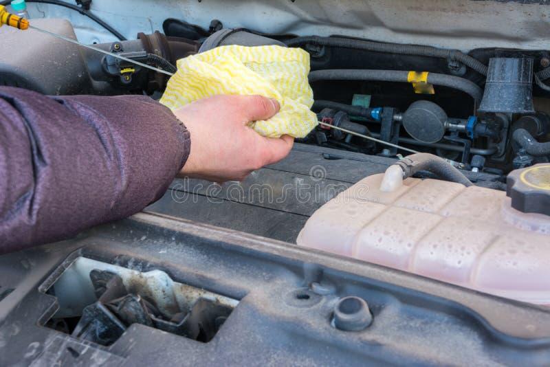 Zbliżenie Samochodowego mechanika ręka ciągnie motorowego oleju dipstick dla sprawdzać parowozowego nafcianego poziom w parowozow obraz royalty free