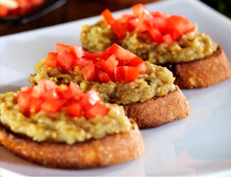 Zbliżenie skorupiasty bruschetta z oberżynami i siekającymi pomidorami obraz royalty free