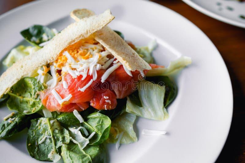 Zbliżenie smakowitego grilla jarscy plasterki uwędzony łosoś z chlebem, letuce arugula i serem w europejczyka stylu, posiłek na w fotografia stock